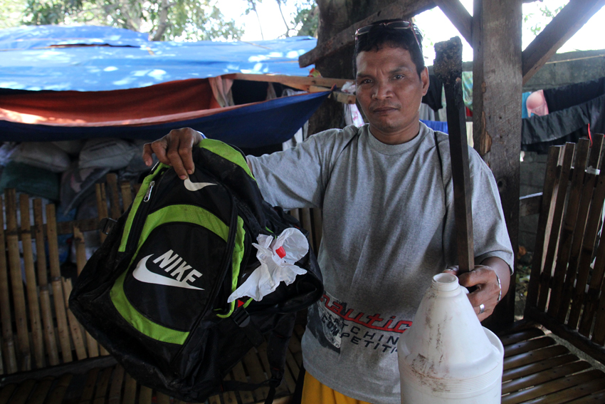 Datu Mintroso Malibato, chairperson of Karadyawan, a lumad organization from Kapalong, Davao del Norte shows a backpack with 1.5 liters of gasoline that was seen at the back of the burned student dormitory. (Photo by Ace Morandante/davaotoday.com)