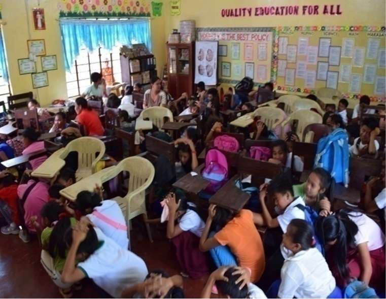 QUAKE DRILL. Students perform the earthquake drill in one of the Oplan ANDAM caravans. (Photo courtesy of Davao del Norte PDRRM.)