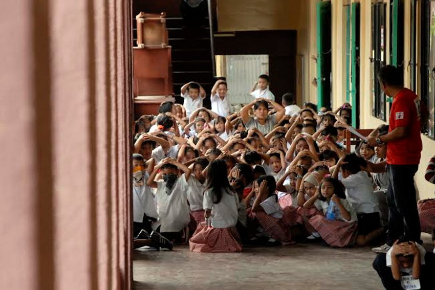 Grade 5 pupils along with their teacher in Sta. Ana Elementary School gather outside their classroom during the dry-run of the nationwide earthquake drill, Tuesday morning. (Ace R. Morandante/davaotoday.com)