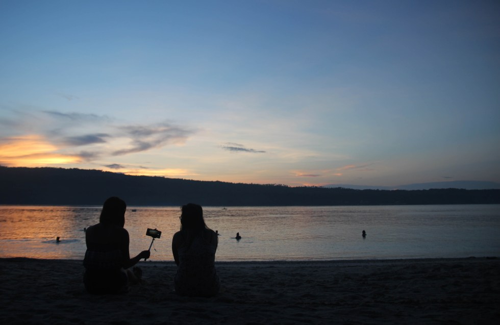 WAITING FOR SUNRISE. As early as 5:00 am, these two young ladies sit on the sand with a camera to wait for sunrise at the Isla Reta beach resort in the Island Garden City of Samal. (Medel V. Hernani/davaotoday.com)