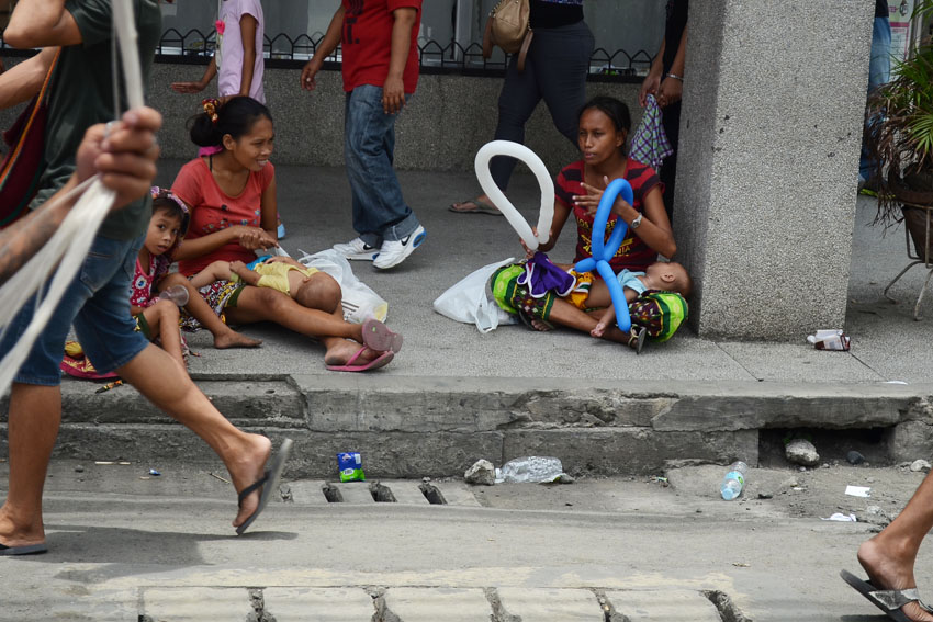SAMA BADJAO WOMEN. Sama Badjao women with their children sit along C.M. Recto street in Davao City to ask for alms from passersby during the floral float parade  on Sunday, August 21, 2016. The Sama Badjao is one of the 11 tribes in the city for whom the Kadayawan celebration is dedicated, however, their plight has yet to be addressed by the government.