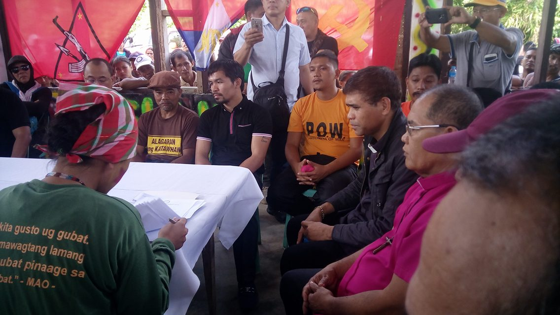 Senator Manny Pacquiao with church leaders from the Exodus for Justice and Peace wait as a member of the New People's Army prepare the release orders of its two prisoners. (Earl O. Condeza/davaotoday.com)