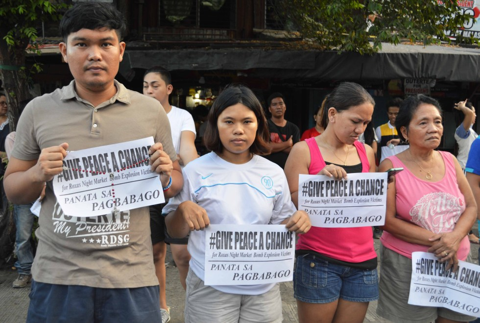 People in neighboring barangays near the blast site join the mass for the victims in Roxas Avenue, Davao City. They asked to give peace a chance.