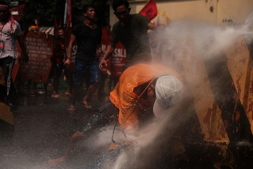 A protester receives the full might of a water cannon fired at him from the Army's national headquarters, Camp Aguinaldo in Quezon City during a protest rally led by national minority alliance group SANDUGO on Tuesday, October 18. (Paulo C. Rizal/davaotoday.com)