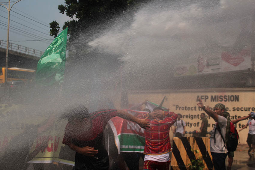 DISPERSAL. Soldiers use water cannons to disperse Lumad and Moro activists protesting in front of the Armed Forces of the Philippines headquarters in Quezon City on Oct. 18.