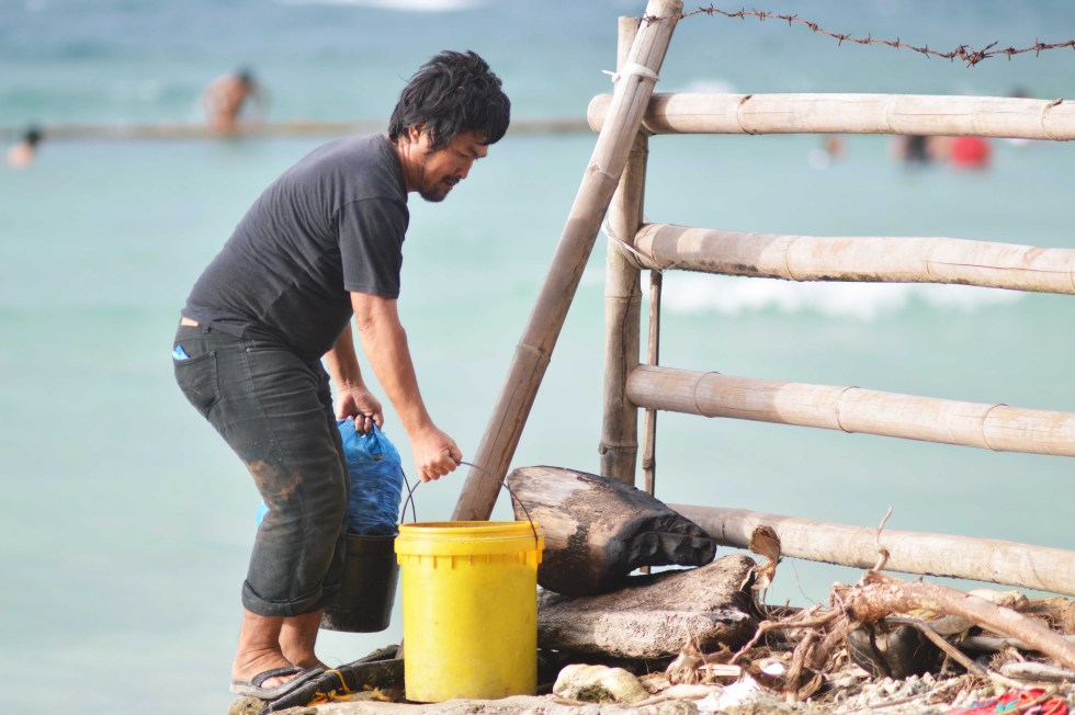 A seafood peddler finds a way to pass through  a private  beach resort in the Island Garden City of Samal to avoid paying the entrance fee. Residents in the area sell fresh seafoods to tourists at a very low price. (Medel V. Hernani/davaotoday.com)