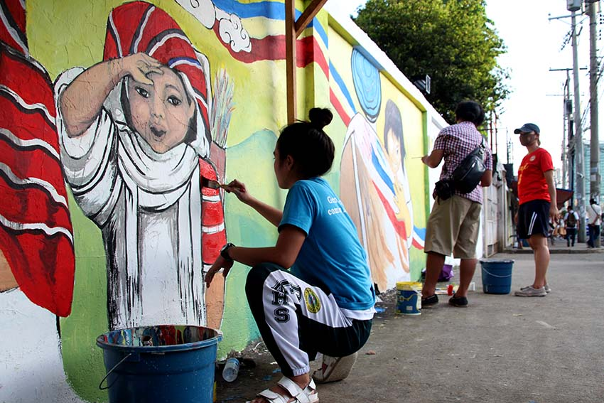 FAMILY. An artist paints a child going to church as part of the mural painting organized by the Inter-Agency Council Against Human Trafficking. (Paulo C. Rizal/davaotoday.com)