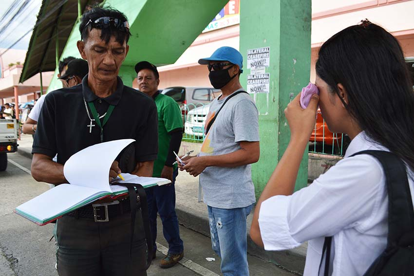 A traffic enforcer gives a citation ticket to a student in Davao City after she crosses the street. At least four pedestrians have been apprehended on Friday afternoon, Dec. 2, along JP Laurel Street in Davao City after they violated the Anti-Jaywalking ordinance. Violators are obliged to undergo seminar and pay fine of P100 or render community service thru City Social Services and Development Office. (Medel V. Hernani/davaotoday.com)