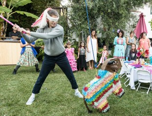 Photo of girl hitting Fiesta piñata