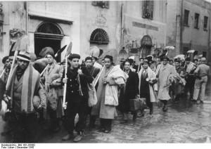 """""""לעם אלמן בתוך תוניס, כלה עשו וכל אונס"""" (""""היטלר הרשע ופעולותיו""""). יהודי העיר תוניס מובלים לעבודות כפייה בעת מלחמת העולם השנייה, דצמבר 1942."""