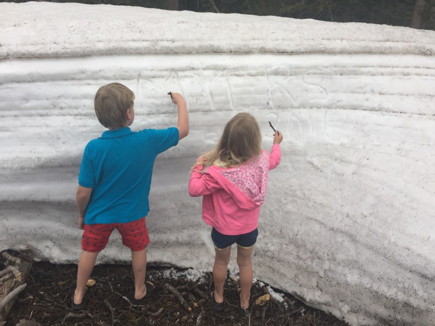 Writing their names in the snow bank.