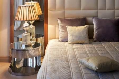 schlafzimmer farbideen creme wandpolsterung lila kissen