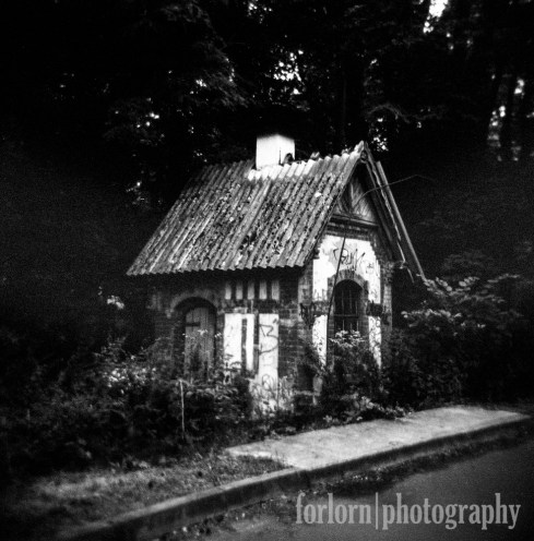 "Finally, as we were walking down the road back to the car, I took this Holga shot (which came out a little too dark because of the woods) of one of the many adorable little houses that were places out in the woods and which were used to pump ""clean air"" into the Sanatorium buildings. Isn't that sweet? Camera: Holga 120N Film: Kodak Tri-X"