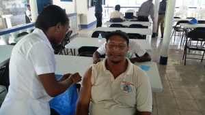 GWI Employee receiving a vacination from a Ministry of Health Representative