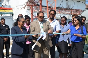 Prime Minister Moses Nagamootoo assisted by NCN's Chief Executive Officer, Molly Hassan cut the ceremonial ribbon to commission the Satellite Earth Station Multimedia Teleport at NCN