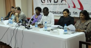 Chairman of the Board of Directors of the Guyana National Broadcasting Authority, Leonard Craig (white long sleeved shirt) flanked by other members of the Board at a news conference.