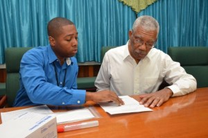 Mr. Shawn Manbodh, Quality Manager and Medical Technologist explains to President David Granger what information will be garnered from the results of the Ancestry DNA test