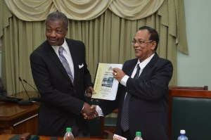 Dr. Barton Scotland, C.C.H, MP receiving the Auditor General Report from Deodat Sharma, Auditor General of Guyana. (GINA photo)