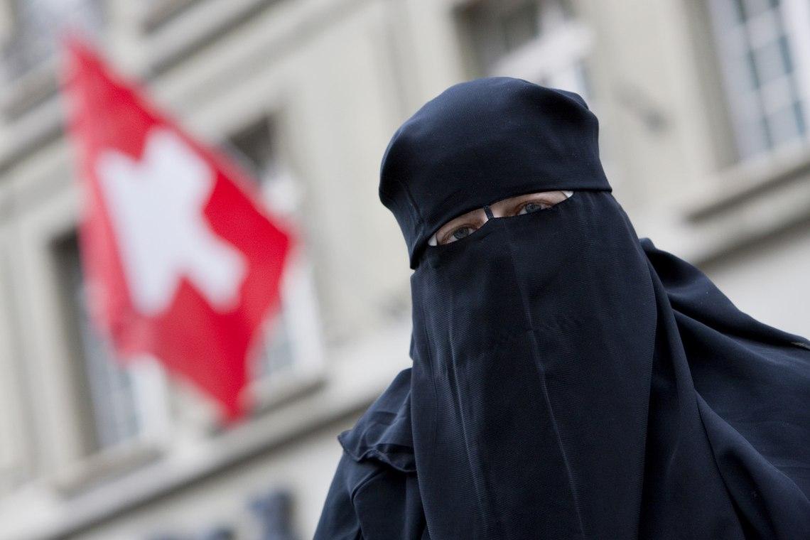Warum sie zur Osterzeit Eier essen soll, ist ihr schleierhaft: grauenhaft plakativ fotografierte Muslima vor einer Schweizer Flagge. Bild: KEYSTONE