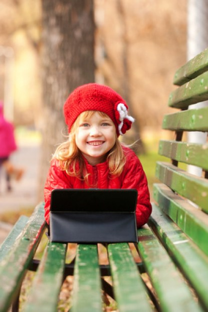 Happy smiling little girl  with tablet pc