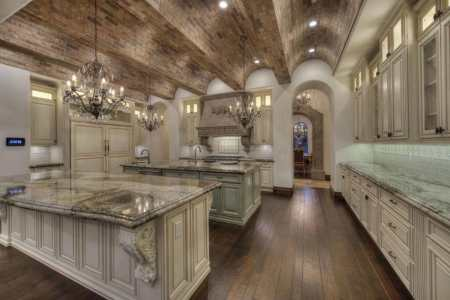 luxury mediterranean kitchen with arched brick ceiling off white cabinetry and crystal chandeliers