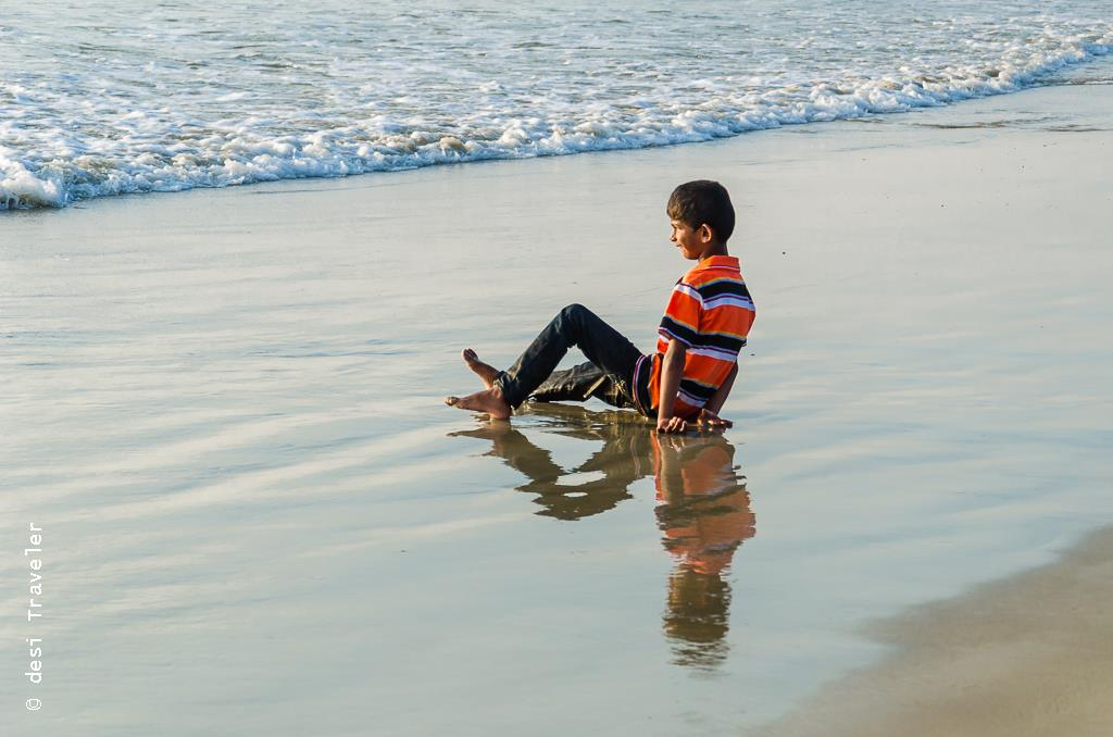 A boy enjoys sunset on Goa Beach