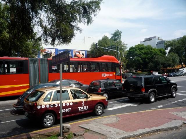 Taxi capitalino y, de fondo, el metrobus, sobre avenida Insurgentes Sur