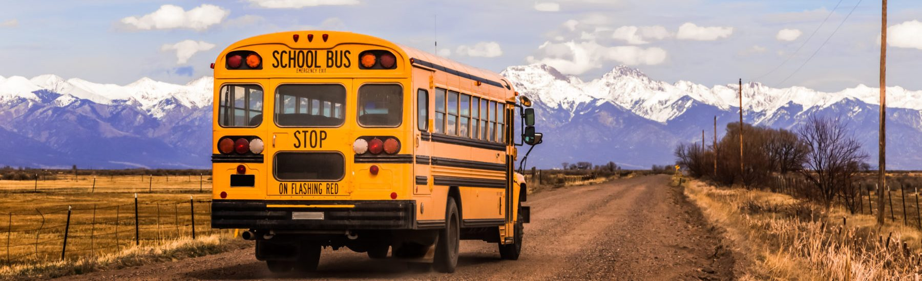 Yellow school bus on a country road, with snow-covered mountains in the background.