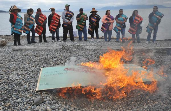 """Members of the Lummi Nation protest the proposed coal export terminal at Cherry Point by burning a large check stamped """"Non-Negotiable."""" The tribe says they want to protect the natural and cultural heritage of the site.  Photo by Indian Country Today Media Network."""