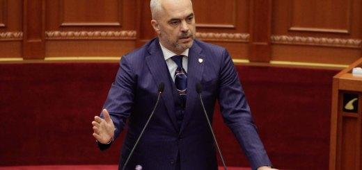 """Kryeministri Edi Rama, duke folur gjate nje seance parlamentare, ku eshte miratuar heqja e imunitetit te dy deputeteve, Tom Doshi dhe Mark Frroku. Ky vendim i hap rrugen kerkeses se Prokurorise se Pergjithshme per dhenien e autorizimit per arrestimin e dy deputeteve, te akuzuar """"per deshmi te rreme""""./r/n/r/nPrime Minister Edi Rama, speaks during a parliamentary session."""