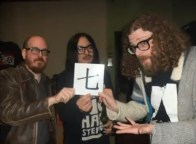 "Beards and long hair holding up the Chinese character for ""7"" in a Death to Giants music video."