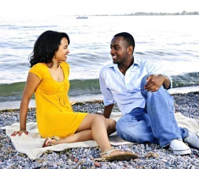 Young romantic couple looking at each other sitting on beach