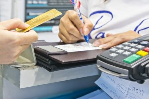 woman customer shopping in department store and paying by credit card