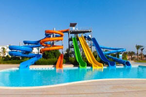 Colorful water slides in water park pool on beautiful summer day. No people, vibrant colors.