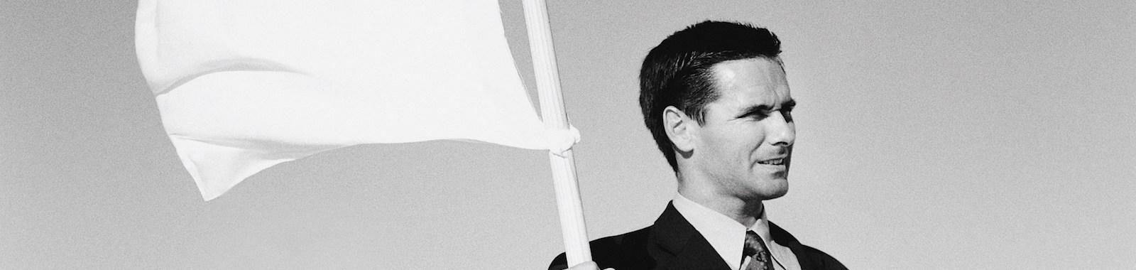 Businessman holding white flag