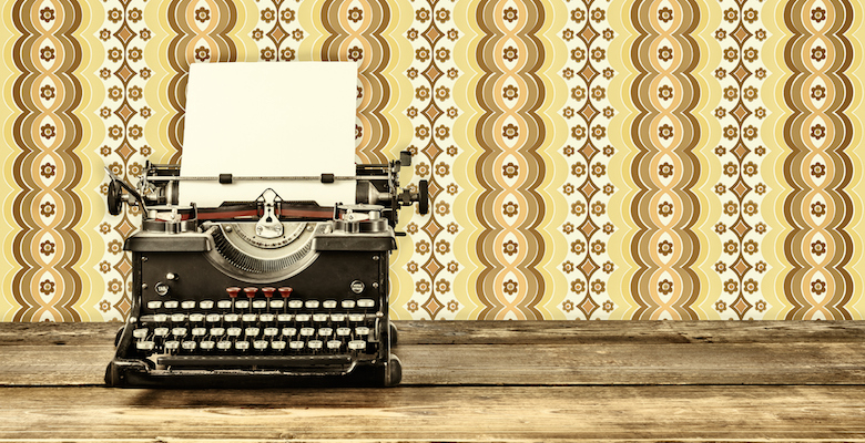 Retro styled image of an old typewriter with blank paper sheet on a wooden table with vintage wallpaper behind it