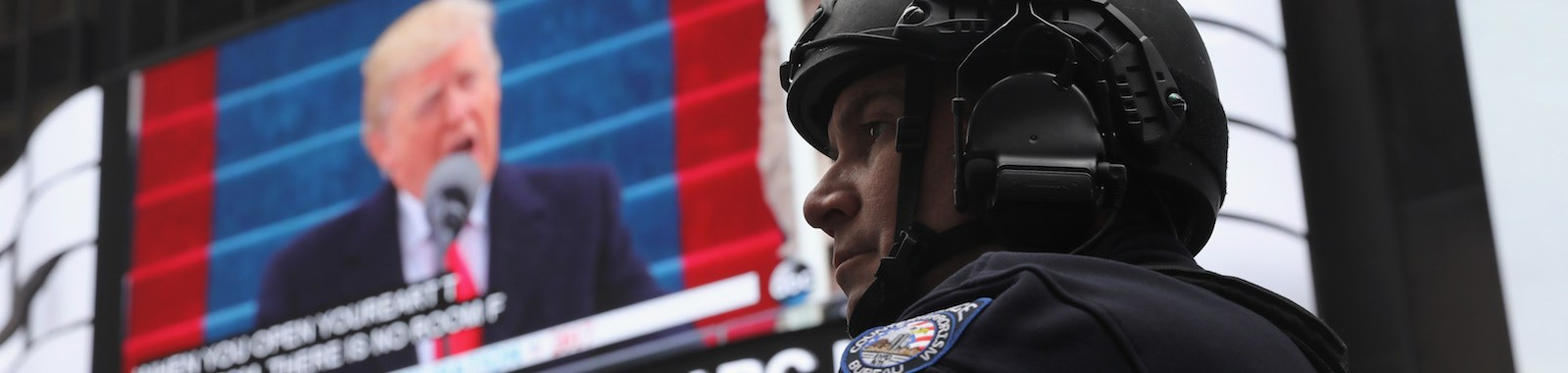 NEW YORK, NY - JANUARY 20:  A New York City policeman stands guard during the televised inauguration of Donald Trump as the 45th President of the United States while in Times Square on January 20, 2017 in New York City. People gathered at the iconic Manhattan site to watch the event outside on a large screen.  (Photo by John Moore/Getty Images)