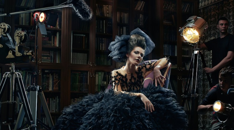 Lady wearing a gorgeous old-fashion dress is sitting on the chair while people around her seem to be preparing for action. Furry mic, moody lights and all kinds of crazy modern thighs standing around.