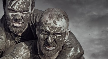 Shaved man carrying friend during a mud run