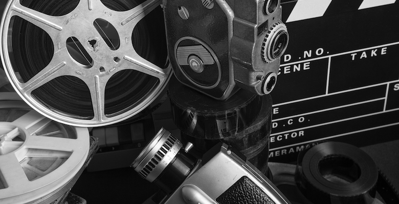 Old fashioned 8mm film projector,film camera,film reels,film slate (clapper),microphone and books On desk.The image was shot close up with a full frame DSLR camera in color and edited to black and white.It was shot in studio.No people are seen in photo.