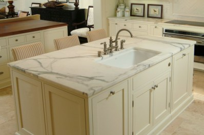 White coastal style kitchen with two islands, off white cabinets, travertine tile floors, carrera marble counter tops, white paneling on walls, herringbone tile backsplash at cooktop