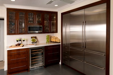contemporary kitchen wine bar with microwave mounted in wall cabinet shelf, water texture glass cabinet doors, sub zero refrigerators and wine cooler