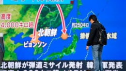 A man stands in front of a huge screen showing TV news program reporting North Korea's missile launch, in Tokyo, Wednesday, Nov. 29, 2017. (AP)
