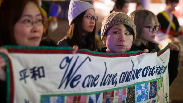Women hold a quilt with messages written on it during a protest outside the site of a summit on North Korea, hosted by Canada and the U.S. in Vancouver, British Columbia, Monday, Jan. 15, 2018. (AP)