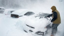 Heavy winds blow snow as Ryan Foster, 25, scrapes snow from his car in the parking lot where he lives at the Donner Summit Lodge in Norden on Thursday, March 1, 2018, near Donner Summit, Calif. (AP)