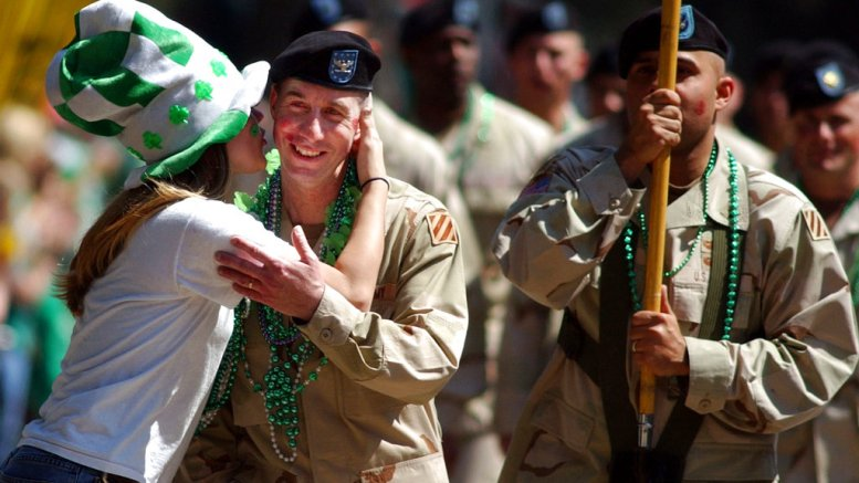 In this Friday, March 17, 2006, file photo, U.S. Army Col. Ronald Tuggle is kissed while marching with his unit of the Army's 3rd Infantry Division in Savannah, Ga., during the annual St. Patrick's Day parade. (AP)