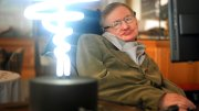 In this Feb. 25, 2012 photo, Professor Stephen Hawking poses beside a lamp titled 'black hole light' by inventor Mark Champkins, presented to him during his visit to the Science Museum in London. (AP)