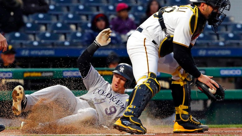 Colorado Rockies' DJ LeMahieu (9) scores on a single by Colorado Rockies' Chris Iannetta as Pittsburgh Pirates catcher Francisco Cervelli takes the late relay throw during the first inning of a baseball game in Pittsburgh, Monday, April 16, 2018. (AP)