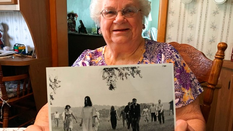 """In this April 21, 2018 photo, Ella Mae Smith, 86, of Evans City, P.a, poses with a publicity photo from the horror movie """"Night of the Living Dead.""""  (Jason Nark/The Philadelphia Inquirer via AP)"""