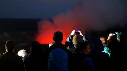 Visitors take pictures as Kilauea's summit crater glows red in Volcanoes National Park, Hawaii, Wednesday, May 9, 2018. (AP)